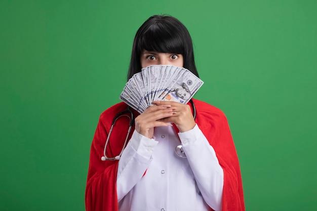 Überraschtes junges superheldenmädchen, das stethoskop mit medizinischem gewand und umhang trägt gesicht bedeckt mit bargeld