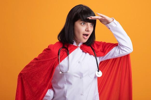 Überraschtes junges superheldenmädchen, das stethoskop mit medizinischem gewand und umhang trägt und entfernung mit hand lokalisiert auf orange betrachtet