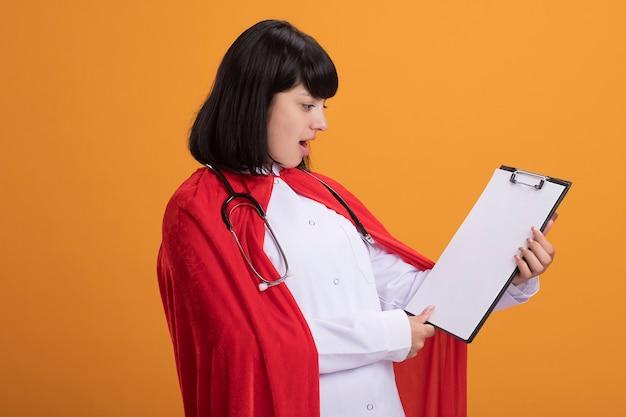 Überraschtes junges superheldenmädchen, das stethoskop mit medizinischer robe und umhang trägt, die zwischenablage halten und betrachten
