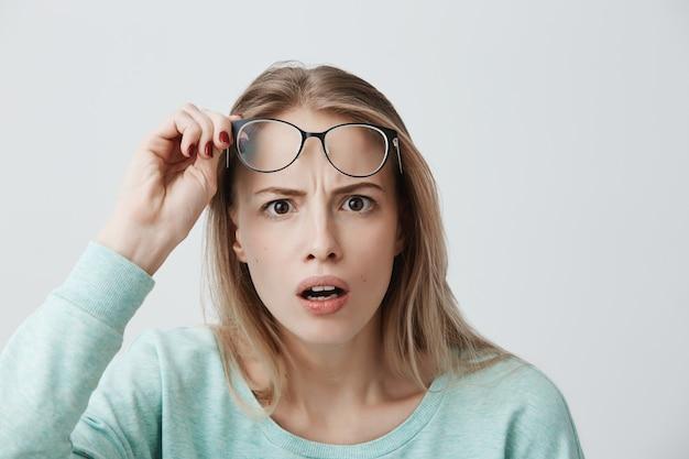 Überraschtes junges weibliches model mit langen blonden haaren, brille und blauem langarmhemd, sieht entsetzt aus