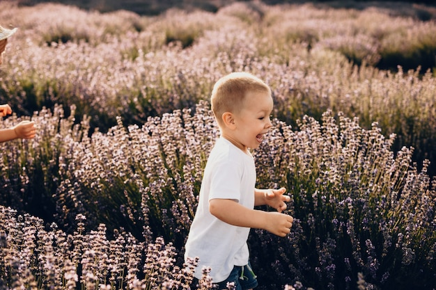Überraschtes kaukasisches kind, das ein weißes t-shirt trägt, läuft glücklich durch ein lavendelfeld