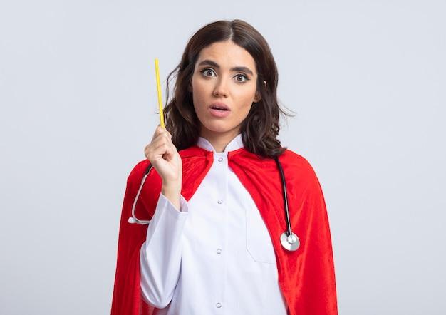 Überraschtes kaukasisches superheldenmädchen in der arztuniform mit rotem umhang und stethoskop hält bleistift