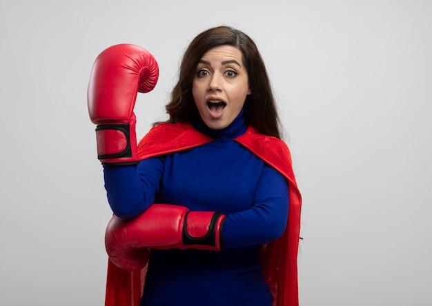 Überraschtes kaukasisches superheldenmädchen mit rotem umhang, der boxhandschuhe trägt, hält hand auf weiß