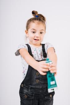 Überraschtes kind mit farbtube in den händen