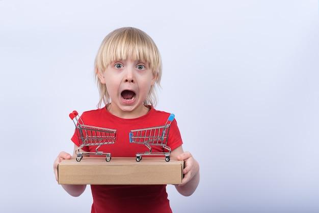 Überraschtes kind mit schachtel und zwei kleinen einkaufswagen auf weißem raum. online-kauf und lieferung nach hause