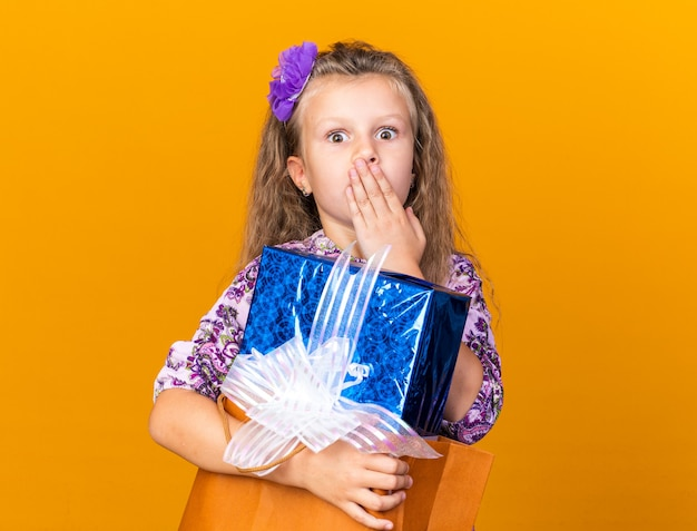 Überraschtes kleines blondes mädchen, das hand auf mund setzt und geschenkbox lokalisiert auf orange wand mit kopienraum hält