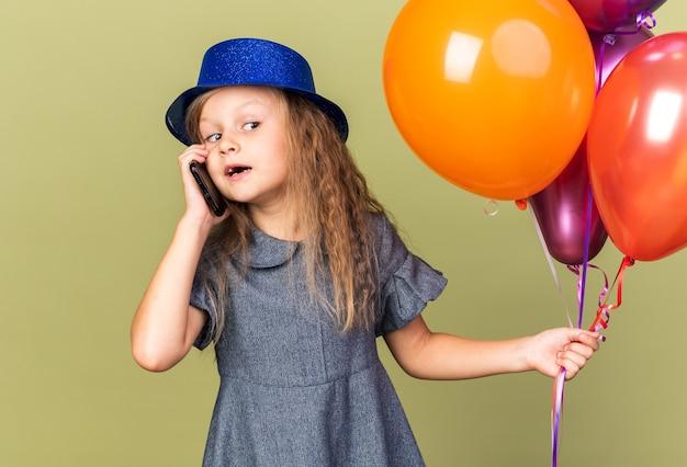 Überraschtes kleines blondes mädchen mit blauem partyhut, der heliumballons hält und telefoniert, isoliert auf olivgrüner wand mit kopienraum