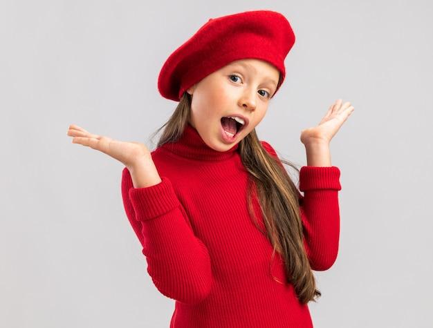 Überraschtes kleines blondes mädchen mit rotem barett, das leere hände in der luft mit offenem mund zeigt, der nach vorne isoliert auf weißer wand schaut