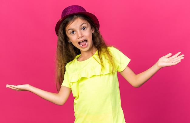 Überraschtes kleines kaukasisches mädchen mit lila partyhut, das die hände isoliert auf rosa wand mit kopierraum hält?