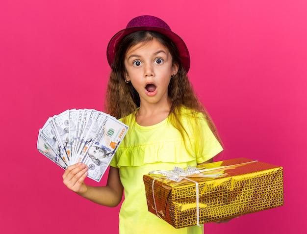 Überraschtes kleines kaukasisches mädchen mit lila partyhut, das geschenkbox und geld isoliert auf rosa wand mit kopienraum hält