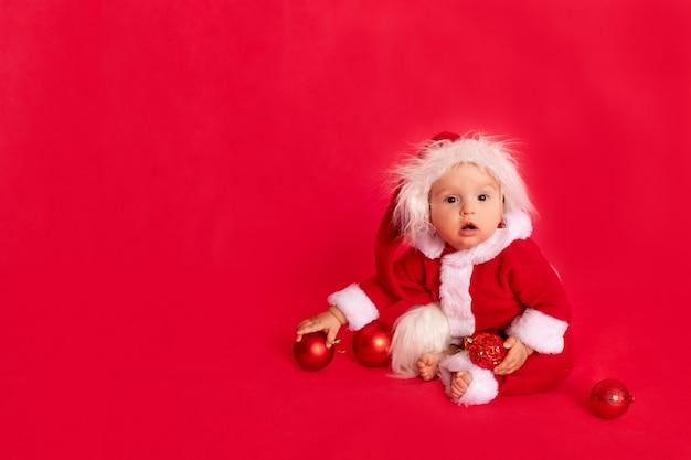 Überraschtes kleines kind in einem weihnachtsmannkostüm sitzt