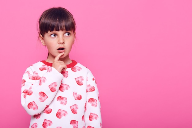 Überraschtes kleines mädchen, das mit weit geöffnetem mund und nahem finger zur seite schaut, kopierraum, pullover tragend, über rosa wand isoliert.