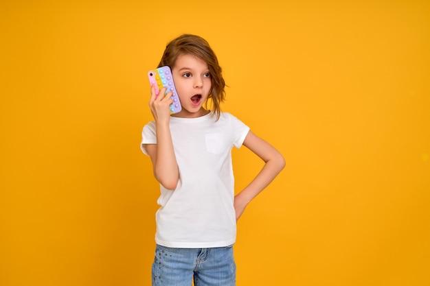 Überraschtes kleines mädchen, das telefon mit offenem mund hält, isoliert über orangefarbenem hintergrund