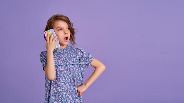 Überraschtes kleines mädchen, das telefon mit offenem mund hält, isoliert über violettem farbhintergrund