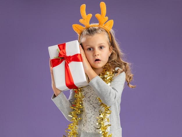 Überraschtes kleines mädchen, das weihnachtshaarreifen mit girlande am hals trägt, die geschenkbox um das gesicht isoliert auf blauer wand hält