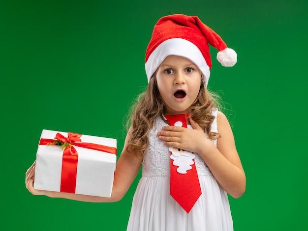 Überraschtes kleines mädchen, das weihnachtsmütze mit krawatte hält, die geschenkbox hält, die hand auf sich lokalisiert auf grünem hintergrund setzt