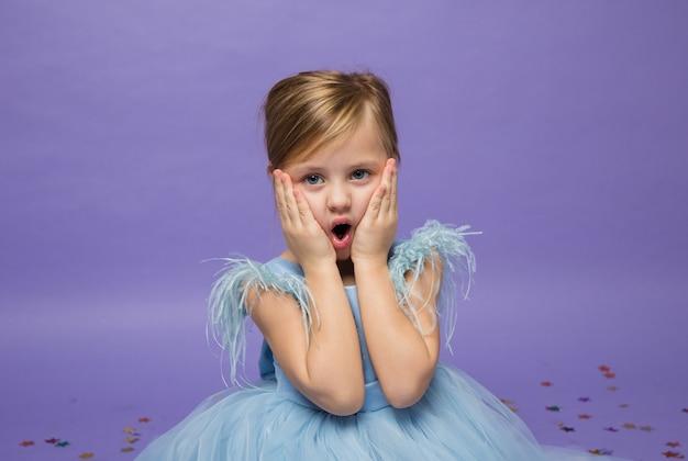 Überraschtes kleines mädchen mit einem blauen kleid auf lila