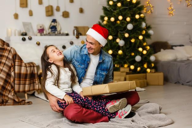 Überraschtes kleines mädchen mit ihrem vater, der ein weihnachtsgeschenk hält
