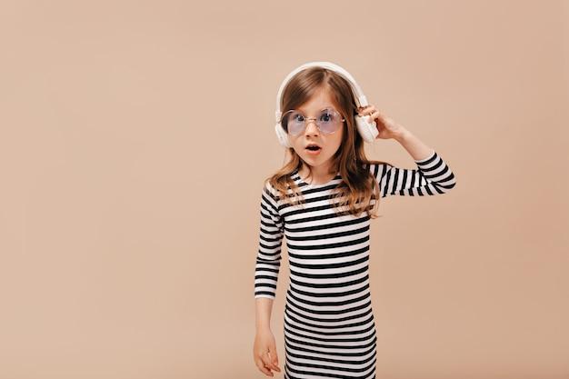 Überraschtes kleines stilvolles mädchen, das abgestreiftes kleid und trendiges rundes glas trägt, das musik hört und zur kamera aufwirft