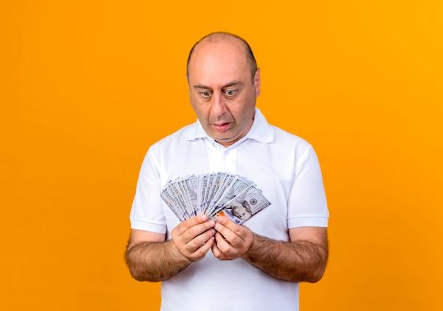 Überraschtes lässiges reifes mannhalten, das bargeld lokalisiert auf gelb hält und betrachtet
