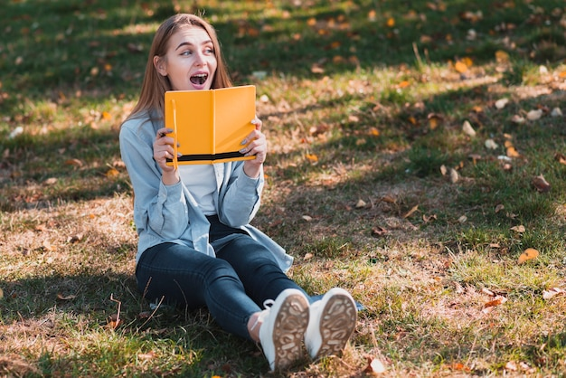 Überraschtes mädchen, das ein gelbes notizbuch hält