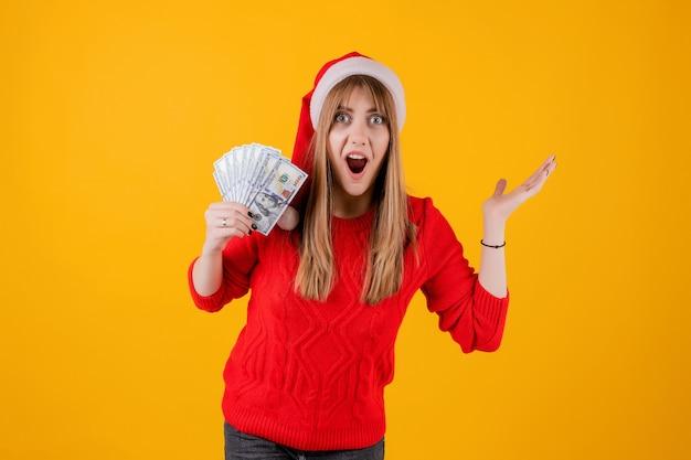 Überraschtes mädchen, das hundert dollarscheine in der hand trägt sankt-hut hält