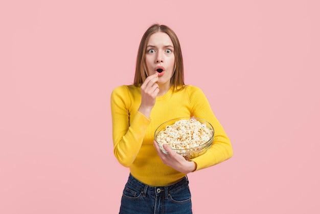 Überraschtes mädchen, das popcorn isst