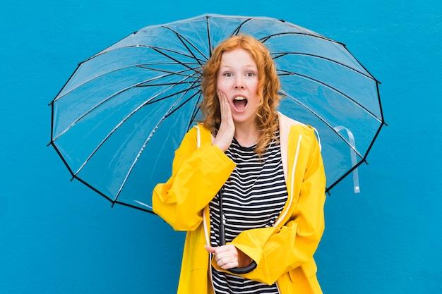 Überraschtes mädchen, das regenschirm hält