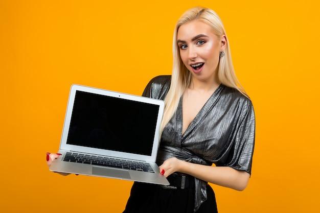 Überraschtes mädchen hält laptop mit vorlage für webseite auf gelbem hintergrund