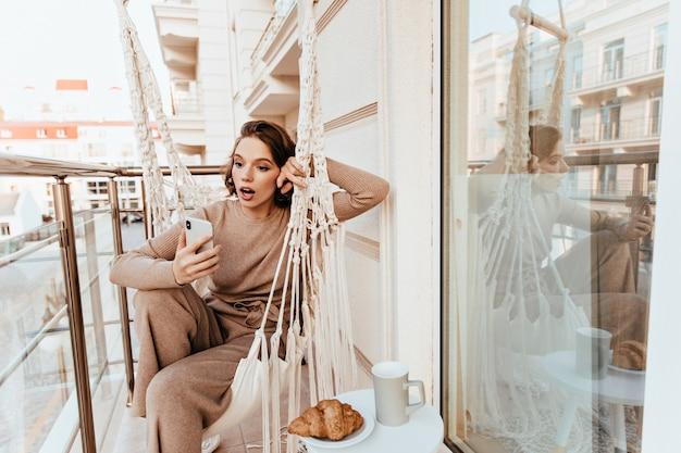 Überraschtes mädchen im braunen pullover, der mit telefon am balkon aufwirft. erstaunliche charmante dame beim mittagessen auf der terrasse.