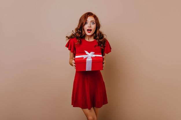 Überraschtes mädchen im kurzen roten kleid, das geschenk hält. entzückende langhaarige frau, die neujahrsgeschenke vorbereitet.