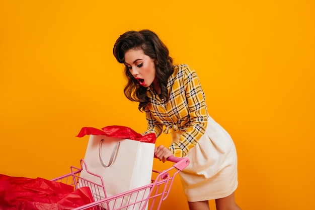 Überraschtes mädchen in der weinlesekleidung, die in einkaufstasche schaut. studioaufnahme der verblüfften pinup-dame, die auf gelbem hintergrund aufwirft.