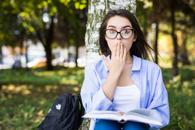 Überraschtes mädchen in jeansjacke und brille liest buch gegen sommergrünpark.