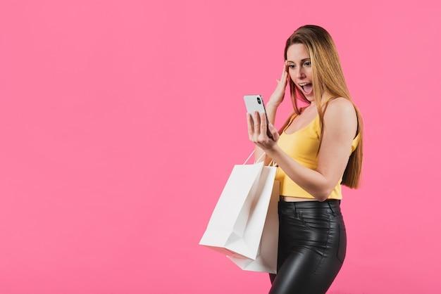 Überraschtes mädchen mit den einkaufstaschen, die telefon betrachten