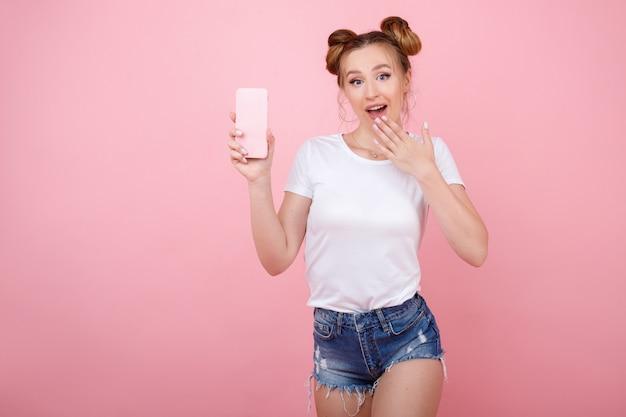Überraschtes mädchen mit einem telefon auf einem rosa raum