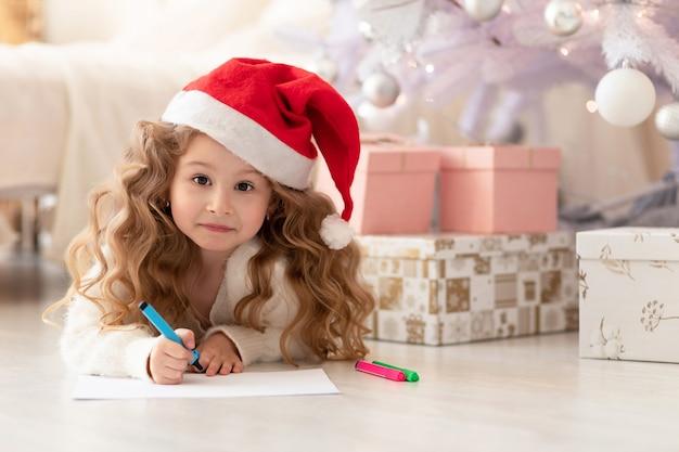 Überraschtes, nachdenkliches kleines mädchen mit rotem hut, das einen brief an den weihnachtsmann schreibt