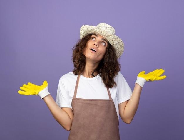 Überraschtes nachschlagen der jungen gärtnerin in uniform mit gartenhut und handschuhen, die hände ausbreiten Kostenlose Fotos
