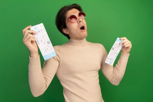 Überraschtes nachschlagen des jungen gutaussehenden mannes, der brillen hält, die tickets lokalisiert auf grüner wand halten