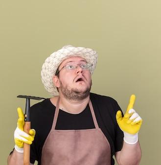 Überraschtes nachschlagen des jungen männlichen gärtners, der gartenhut und handschuhe trägt, die rechenpunkte an oben lokalisiert auf olivgrüner wand mit kopienraum halten
