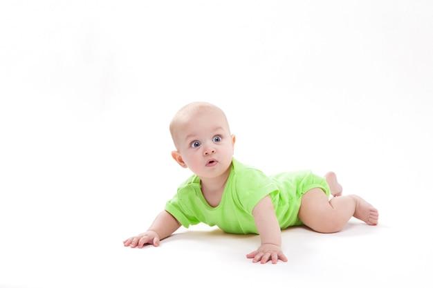 Überraschtes nettes baby, das auf seinem magen liegt
