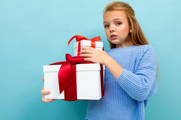Überraschtes nettes schulmädchen auf einem blau mit einem dia von geschenkboxen