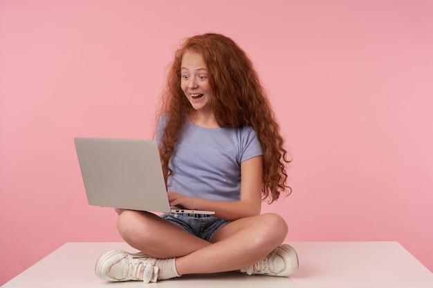 Überraschtes niedliches weibliches kind mit dem lockigen langen haar, das modernen laptop hält und den bildschirm fröhlich betrachtet und hände auf tastatur hält, während mit gekreuzten beinen über rosa hintergrund sitzt