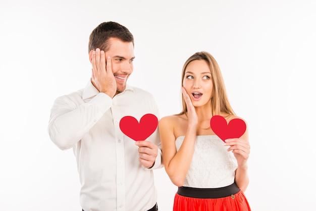 Überraschtes paar verliebt in papierherzen