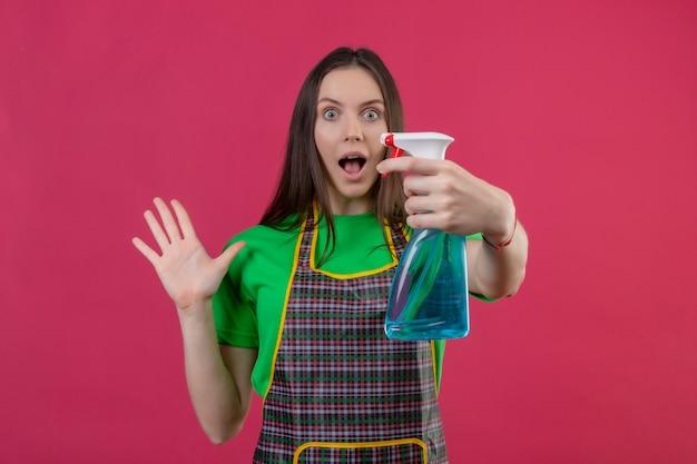 Überraschtes putzendes junges mädchen, das uniform in handschuhen hält, die reinigungsspray, das hand hebt auf lokalisiertem rosa hintergrund hält