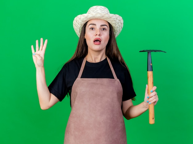 Überraschtes schönes gärtnermädchen in uniform, die gartenhut hält, der rechen hält und vier lokalisiert auf grünem hintergrund zeigt