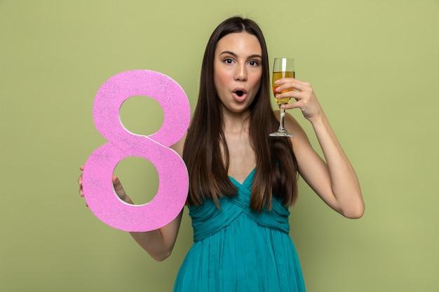 Überraschtes schönes junges mädchen am tag der glücklichen frau, das nummer acht mit einem glas champagner hält, isoliert auf olivgrüner wand