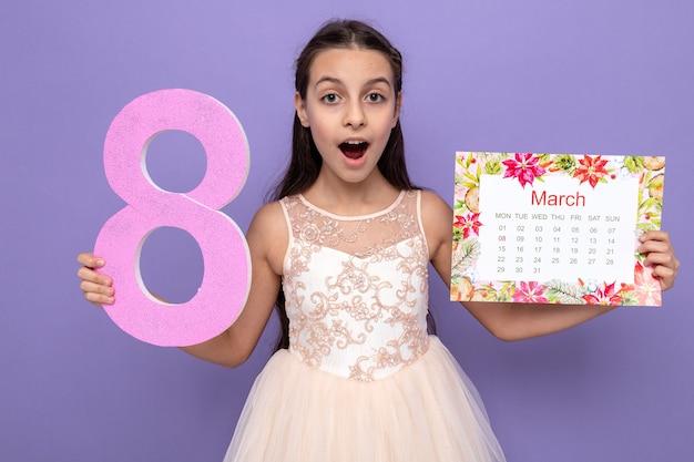 Überraschtes schönes kleines mädchen am glücklichen frauentag, der die nummer acht mit kalender hält