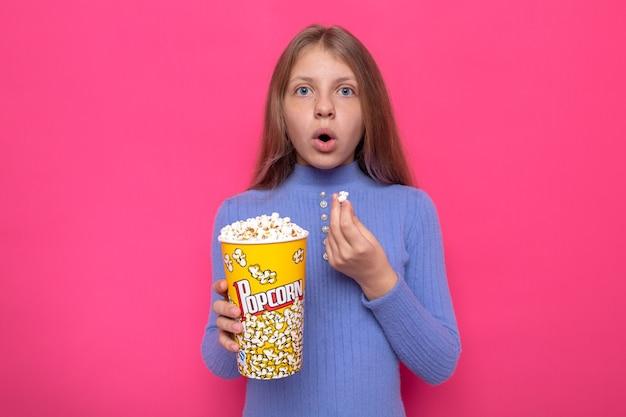 Überraschtes schönes kleines mädchen mit blauem pullover mit popcorn-eimer