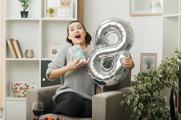 Überraschtes schönes mädchen am glücklichen frauentag, der den ballon nummer acht mit dem geschenk auf dem sessel im wohnzimmer hält