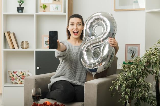 Überraschtes schönes mädchen am glücklichen frauentag, der den ballon nummer acht mit dem telefon hält, das auf einem sessel im wohnzimmer sitzt